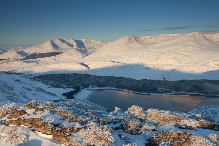 View over Loch Laggan of Creag Megaidh and surrounding mountains in winter,with Binnein Shuas in foreground, Badenoch, Scotland, UK